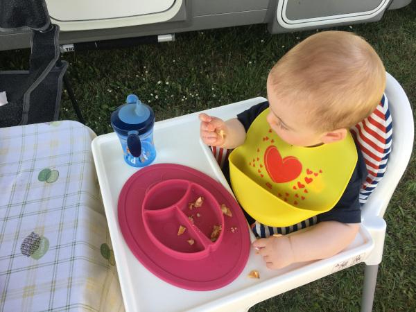 bimbo che mangia sul seggiolone durante lo svezzamento