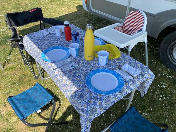 tavola apparecchiata sotto la veranda del camper, senza l'utilizzo di stoviglie usa e getta