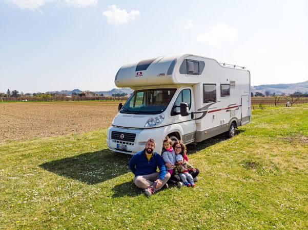 famiglia con due bambini davanti al camper in mezzo al verde