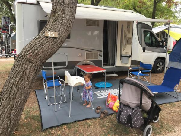 piazzola con camper allestito per l'esterno con tavolo e sedie