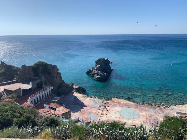 spiaggia vista dall'alto con mare blu e scogli