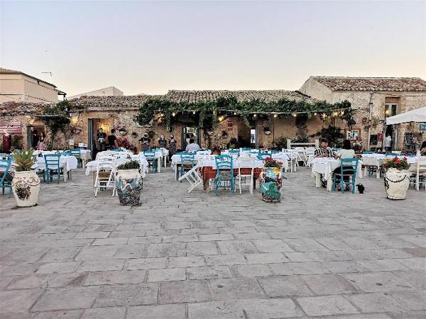 piazza con tavoli e sedie bianche e azzurre