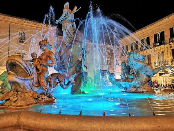 fontana con statue illuminata di notte