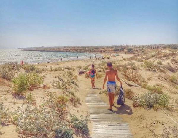 bambini che camminano su passerella per arrivare in spiaggia