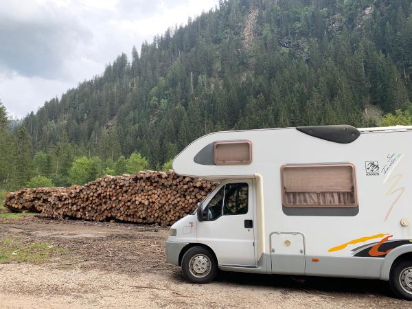 camper parcheggiato davanti a catasta di legna
