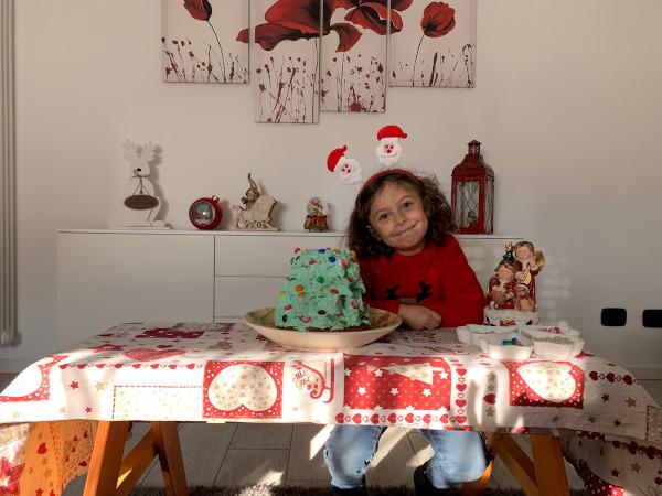 bambina seduta al tavolino con pandoro decorato ad albero di natale