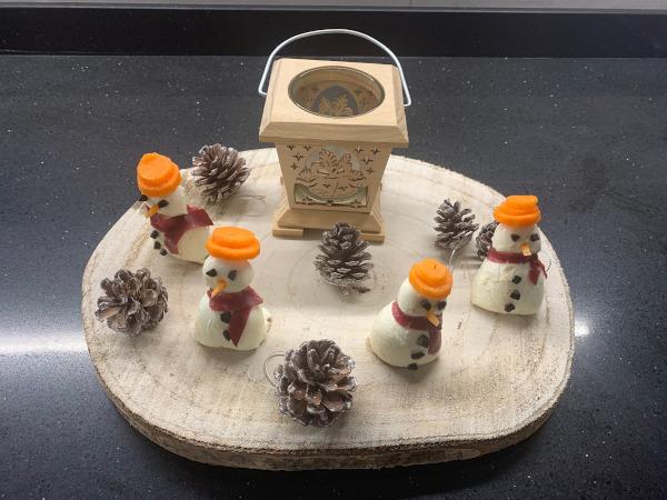 pupazzi di neve con mozzarelle su ceppo di legno