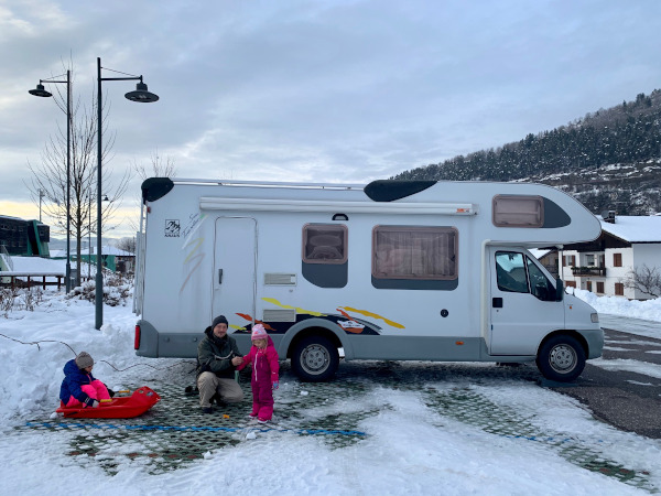 papà con bambine davanti a camper parcheggiato in sosta innevata