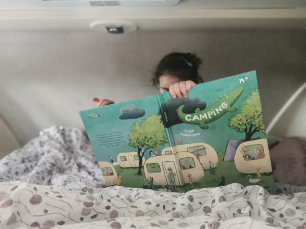 bimba che guarda libro sul lettone del camper