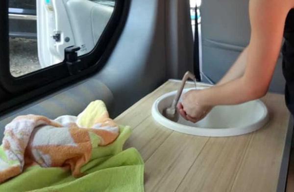 donna che si lava le mani nel lavandino del camper